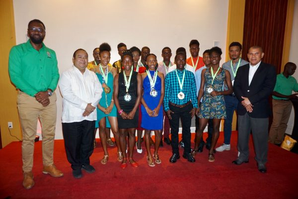 Some members of the successful Track and Field team pose for a photo with Minister of Social Cohesion with responsibility for Culture and Sport, Dr George Norton (right) and Director of Sport Christopher Jones (left) following a welcome home reception at the Pegasus Hotel last night.