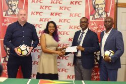 GFF President Wayne Forde (2nd from right) collecting the sponsorship cheque from Charissa Rampersaud, KFC Training Manager, during the launch of the KFC Independence Cup. Also in the photo are the GFF's Technical Director Ian Greenwood (left) and Director of Competitions Ian Alves. (Orlando Charles photo)
