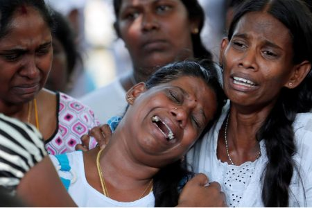People react yesterday during mass burials of victims of a string of suicide bomb attacks in Sri Lanka on Easter Sunday. REUTERS/Dinuka Liyanawatte