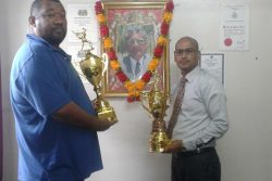 BCB President Hilbert Foster and sponsor Attorney-at-Law Arudranauth Gossai pose with the trophies.