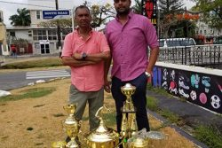 Managing Director of the Trophy Stall, Ramesh Sunich and boss of the JJTRC, Nasrudeen Mohamed Jr. pose with the trophies that will be up for grabs today at the Port Mourant Turf Club.